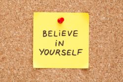 Believe In Yourself, written on an yellow sticky note on a cork bulletin board