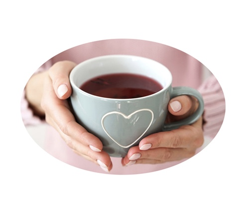 Woman's hands offering coffee  in a mug with a heart